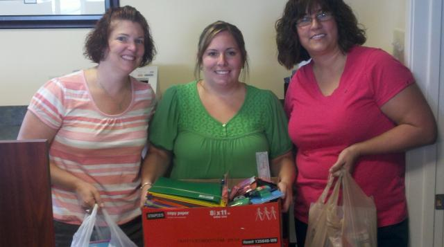 three women pose holding office supplies