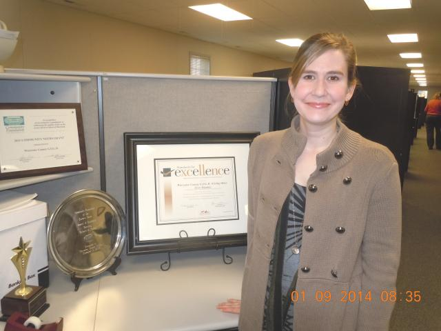 woman stands in cubicle next to excellence award