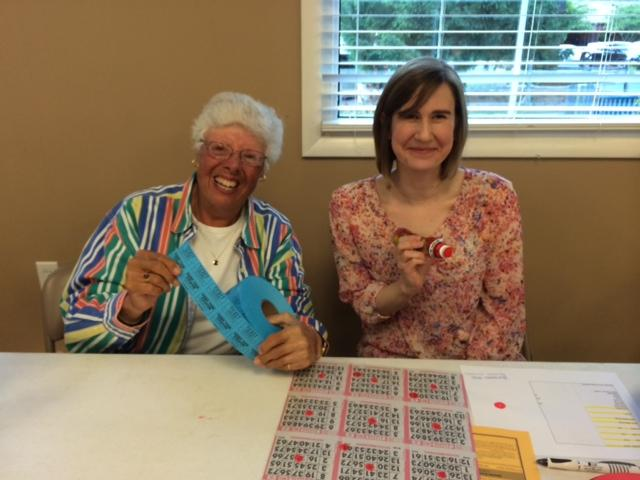 woman holding bingo raffle tickes with another woman with bingo stamp